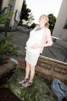 Einfach mal den Bauch halten. In Shirt und Strickjacke von Filippa K, dem Minirock mit Schwangerschaftsbund von Mamalicious und einer Kette von Nicola Hinrichsen