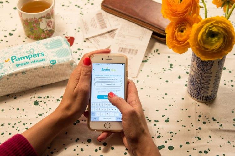 Frau mit Handy testet die neue Pampers-App: Anmeldung