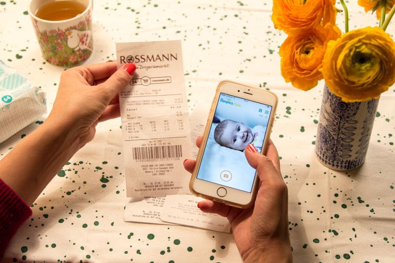 Frau mit Handy testet die neue Pampers-App: Bon und Startseite App