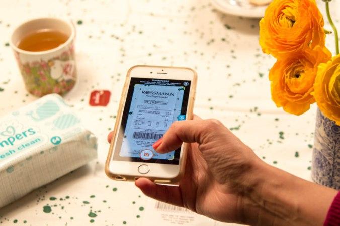 Frau mit Handy testet die neue Pampers-App: Kassen-Bon fotografieren