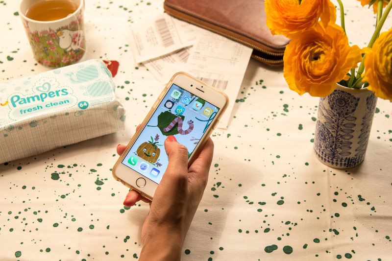 Frau mit Handy testet die neue Pampers-App