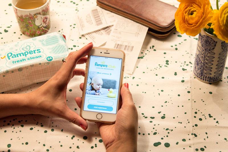 Frau mit Handy testet die neue Pampers-Club-App