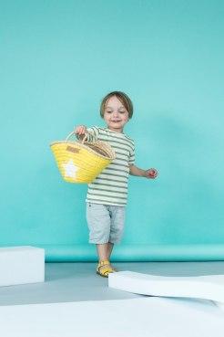 Noam trägt einen gelben Korb, dazu Ringelshirt von Smafolk, Hose Ims&Elfs, Salt-Water sandals