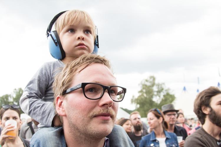 A Summers Tale-Festival mit Kind: Kind mit Gehörschutz auf Papas Schultern