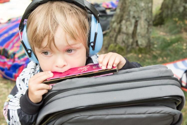 A Summers Tale-Festival mit Kind: Kind spielt Mundharmonika
