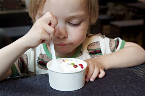 Kind ist frozn Yoghurt im Burger-Grill Peter Pane