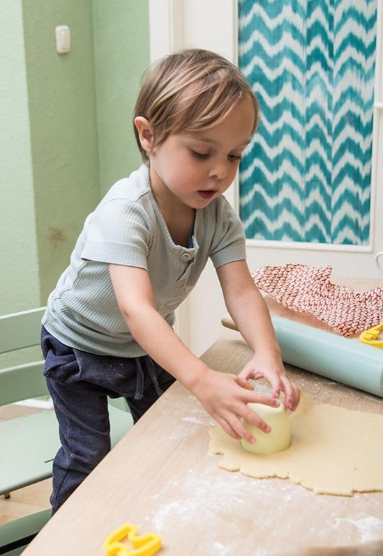 Kind sticht Kekse aus Mürbeteig mit Dinkelmehl