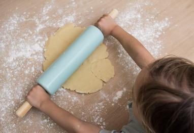 Kind rollt Mürbeteig aus