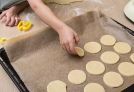Kind legt Kekse auf Backblech