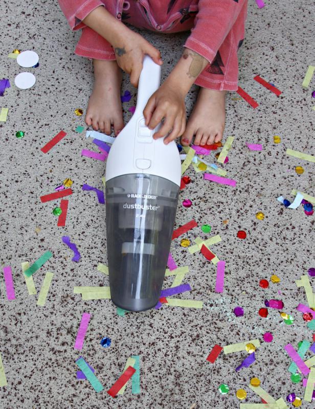 Kind saugt mit dem Handstaubsauger Dustbuster von Black&Decker Konfetti auf