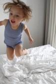 Kind springt auf Bett des Ferienappartments im Dünenhaus in Binz auf Rügen