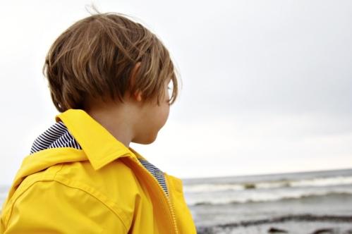 Kind in gelber Regenjacke von Petit Bateau in Binz auf Rügen