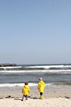 Zwei Kinder mit gelben Regenjacken von Petit Bateau am Strand von Binz auf Rügen