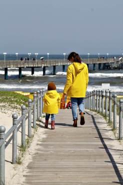 Mutter und Kind mit gelben Regenjacken von Petit Bateau am Strand von Binz auf Rügen