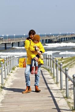 Mutter und Kind mit gelben Regenjacken von Petit Bateau am Strandweg von Binz auf Rügen