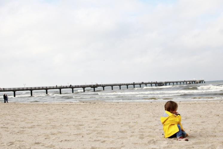 Kind in gelber Regenjacke von Petit Bateau am Strand in Binz auf Rügen
