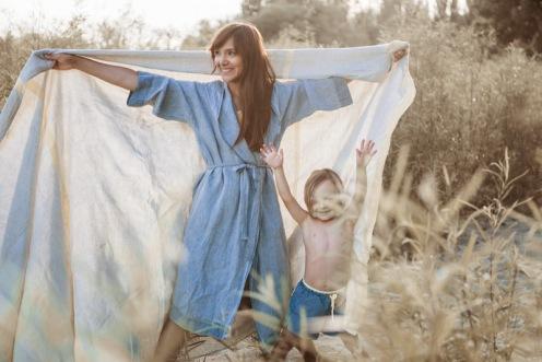 Frau mit Bademantel und Tuch aus Leinen von Kaisu Mari, kleiner Junge i Badehose von Sunuva über Nickis.com