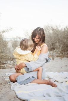 Mutter und Kind innig am Strand. Leinentuch udn Bademantel von Kaisu Mari, Badeanzug One Shoulder von Mymarinin, Kinderbademantel von Trixie baby über Nickis.com
