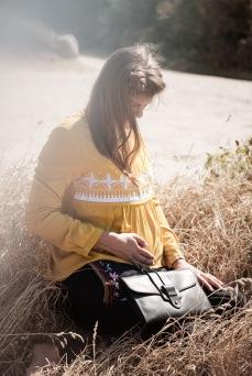 Schwangere Frau trägt Langarmshirt mit Stillfunktion in Senfgelb, dazu Umstandshose von mara Mea udn Clutch von Planet Hiitu