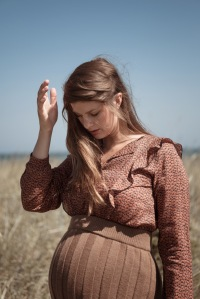 Schwangere Frau trägt Strickrock von Karin Fraidenraij und Bluse mit Rüschen von Lanius