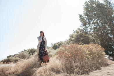 Frau im Trenchcoat und Wickelkleid von Aremed Angels zum Thema nachhaltige Mode, dazu eine Tasche von Planet Hiitu