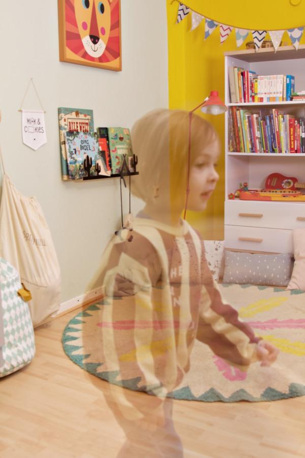 Doppelbelichtung: Kind im bunt eingerichteten Kinderzimmer mit Teppich von Minividuals und Bücherregal von wayfair