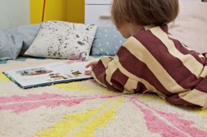 Kind liegt auf rundem fair hergestellte Kinderteppich mit Federmotiv von Minividuals Kids Living