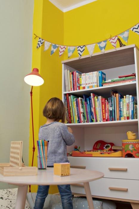 Kinderzimmer Makeover mit Wayfair: Kind sitzt an weißem Buecherregal mit Holzgriffen und Holzfüßen