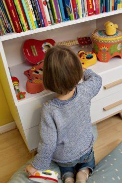 Kinderzimmer Makeover mit Wayfair: Kind sitzt an weißem Buecherregal mit Instrumenten