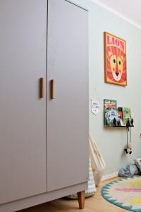 Kinderzimmer Makeover mit Wayfair: grauer Schrank mit Holzfüßen von Meble Vox